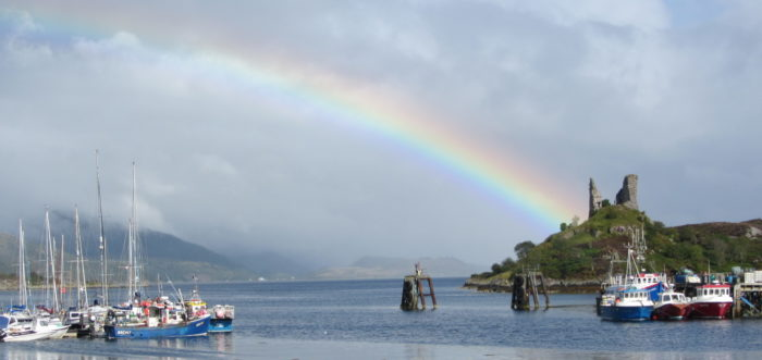 Rainbow at a harbour in Scotland, with a castle ruin in the background